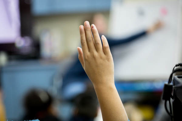 A hand raised in a classroom
