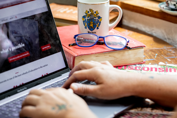 A pair of hands on a laptop, there is a coffee mug, a red book, and blue rimmed glasses in the background