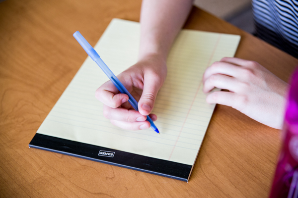A hand holding a pen to write on a yellow ruled notepad