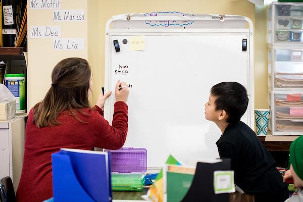 A teacher teaching a child using a white board
